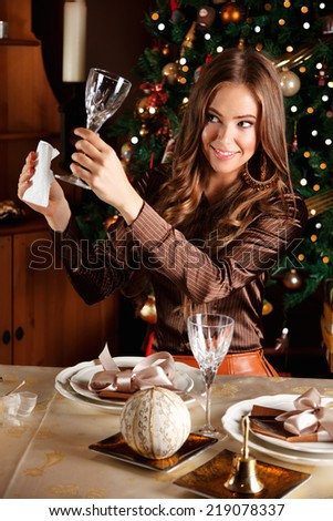 Beautiful young woman cleaning a glass at a well laid Christmas