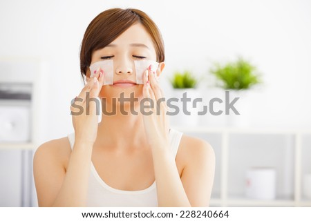Beautiful  young woman cleaning her face with cotton - stock photo