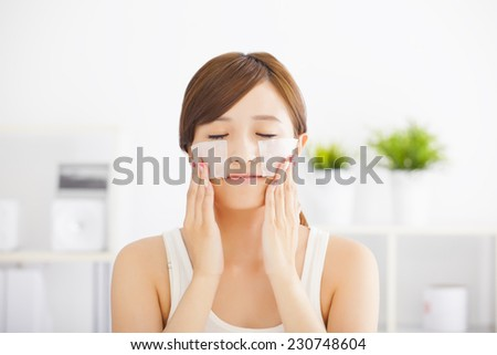 Beautiful  young woman cleaning her face with cotton