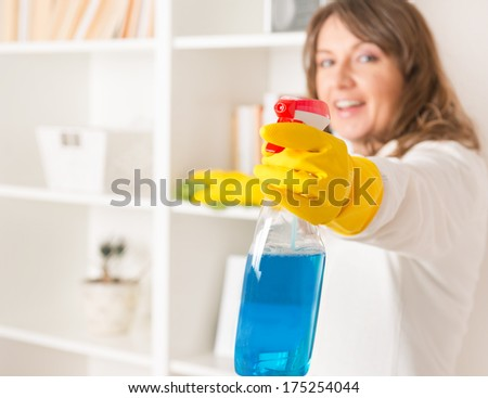 Beautiful young woman cleaning her house wearing yellow gloves with spray cleaners and cloth - stock photo