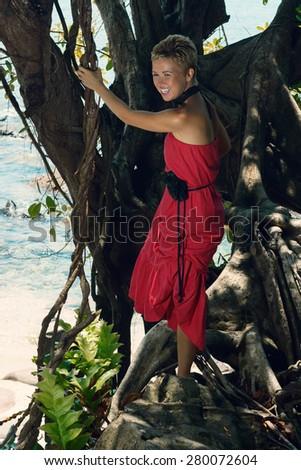 Beautiful young woman climbing a big exotic tree at seashore in long red dress and enjoying beautiful tropical nature view 2 - stock photo