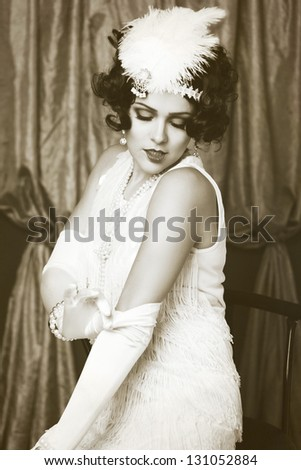 Beautiful young woman close up portrait in retro flapper style headband sepia Vogue style vintage - stock photo