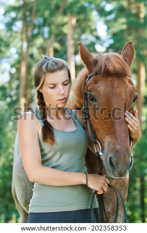 Beautiful young woman close-up with horse, against green of summer park.