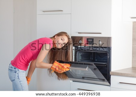 Beautiful young woman cooking in a modern kitchen. A girl prepares food in the oven. - stock photo