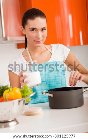 Beautiful young woman cooking in the kitchen, tasting soup