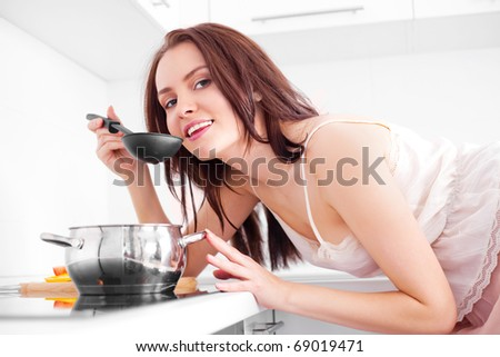 beautiful young woman cooking soup in the kitchen at home