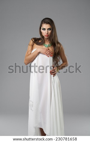 Beautiful young woman covered with white sheet, on gray background