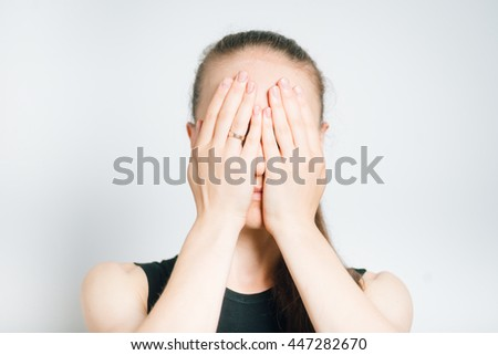 beautiful young woman covers face with hands, isolated on a gray background