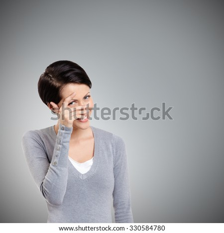 Beautiful young woman covers her eyes with hand, isolated on grey - stock photo