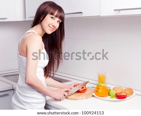beautiful  young woman cutting vegetables for the salad in the kitchen