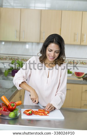 Beautiful Young woman cutting vegetables in the kitchen - stock photo