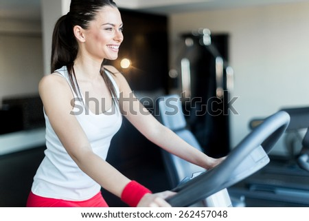 Beautiful, young woman cycling in a gym in order to burn calories fast - stock photo