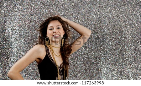 Beautiful young woman dancing at a party against a silver glitter background.