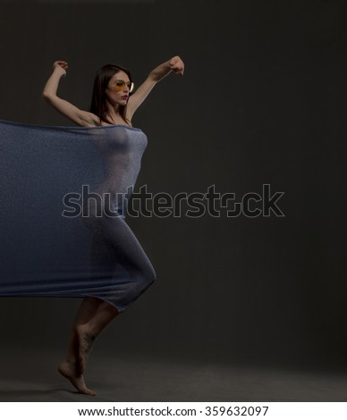 Beautiful young woman dancing with blue fabric on a gray background.