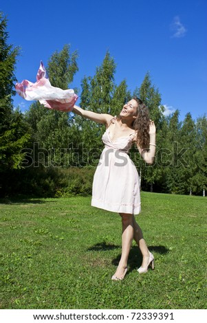 Beautiful young woman dancing with kerchief against the blue sky