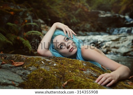 Beautiful young woman day dreaming in the wood. Fantasy and myth - stock photo