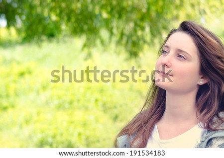 Beautiful young woman daydreaming in a lush green park standing with a serene expression and gentle smile looking up into the air, with copyspace