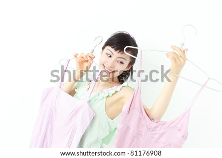 Beautiful young woman deciding what to wear - stock photo