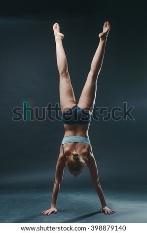 Beautiful young woman do yoga exercise on the dark background