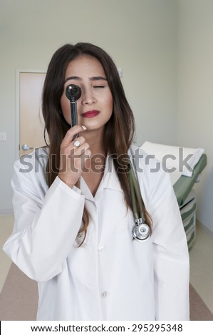 Beautiful young woman doctor holding an otoscope - stock photo