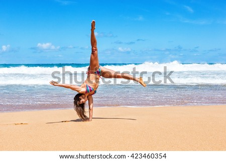 Beautiful young woman doing cart wheels on the beach - stock photo
