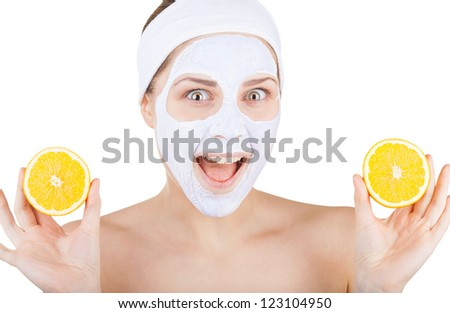 Beautiful young woman doing cosmetic mask on her face with orange isolated on white background - stock photo