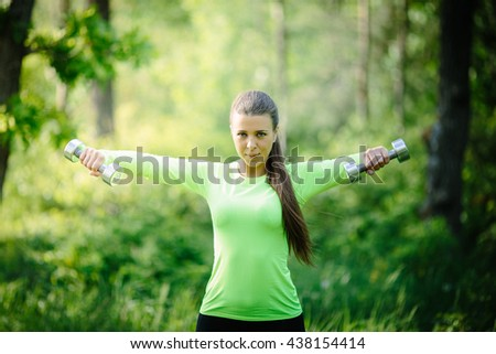 Beautiful young woman doing exercise whith dumbbell in the forest on sunny summer day - stock photo