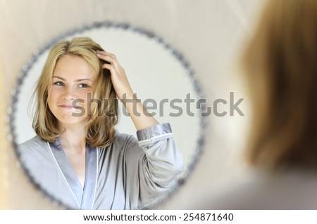 Beautiful young woman doing hair - stock photo
