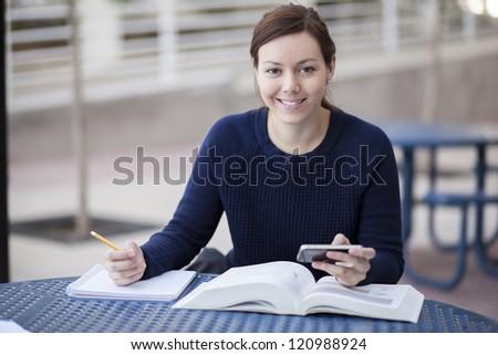 Beautiful young woman doing homework at school - stock photo