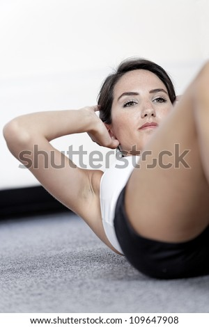 Beautiful young woman doing sit ups at home on the floor - stock photo