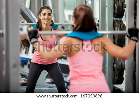 Beautiful young woman doing some squats with a barbell and smiling at the gym - stock photo