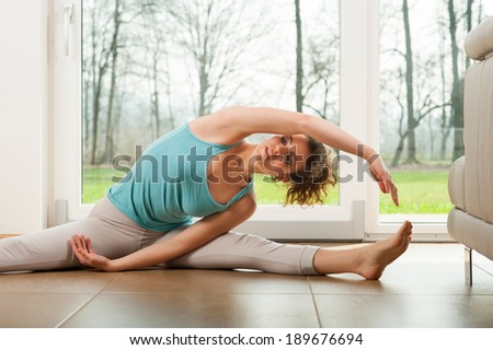 Beautiful young woman doing stretching exercises indoor in front of the big window with beautiful nature view  - stock photo