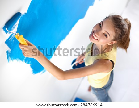 Beautiful young woman doing wall painting . - stock photo
