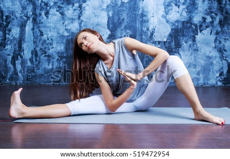 beautiful young woman doing yoga against studio background