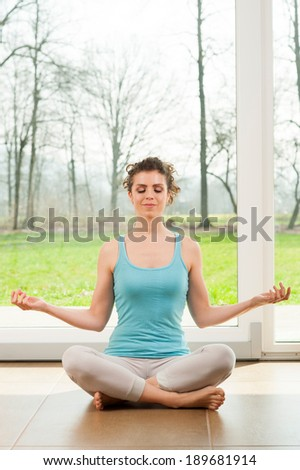 Beautiful young woman doing yoga exercise in her house in front of the big window with a nature view  - stock photo