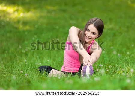 Beautiful young woman doing yoga exercises in the park