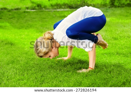 Beautiful young woman doing yoga in the summer park. Healthy lifestyle. Yoga. - stock photo