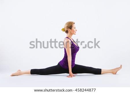 Beautiful young woman doing yoga on a gray studio background