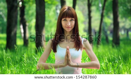 Beautiful young woman doing yoga salutation pose in the forest  - stock photo