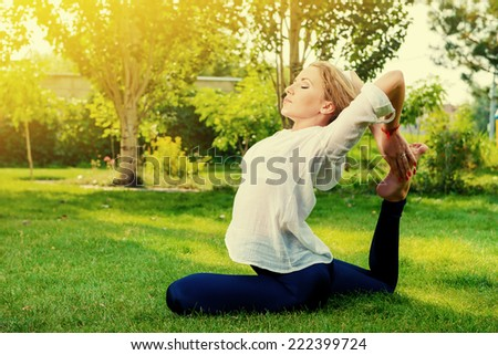 Beautiful young woman doing yoga stretching exercise in the summer park. Healthy lifestyle. Yoga. - stock photo