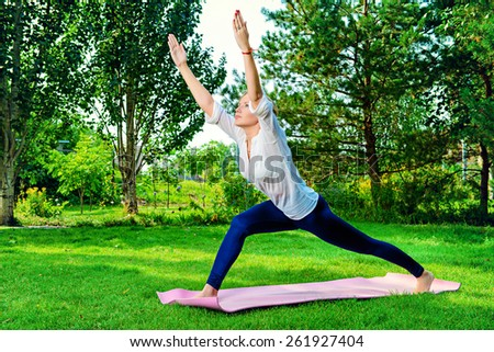 Beautiful young woman doing yoga, stretching exercise in the summer park. Healthy lifestyle. Yoga. - stock photo