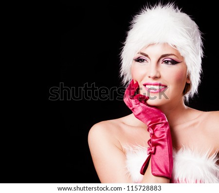 beautiful young woman dressed as Santa, isolated against black background, copy-space to the left