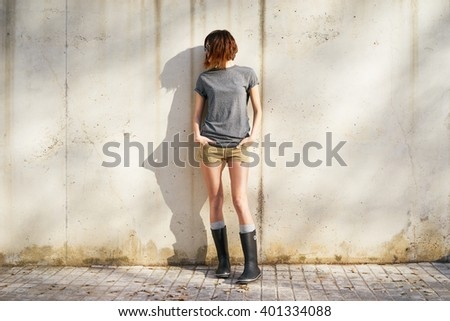 beautiful young woman dressed in a gray blank t-shirt posing against a background of a concrete wall in the rays of the setting sun - stock photo