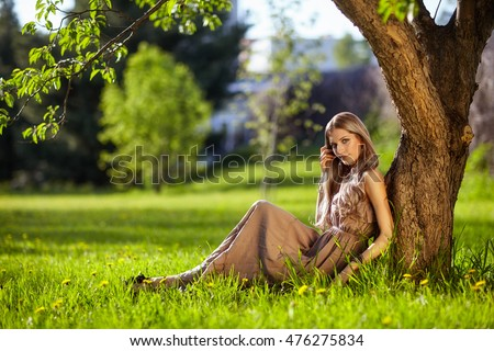 Beautiful young woman dressed in boho style sitting on green grass under apple tree in Spring garden