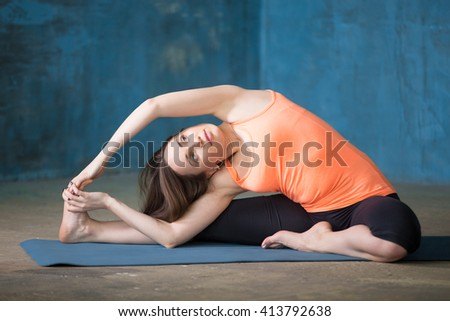 Beautiful young woman dressed in bright sportswear enjoying yoga indoors. Yogi girl working out in grunge interior with blue wall. Parivrtta Janu Sirsasana or Revolved Head-to-Knee Forward Bend Pose - stock photo