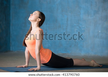 Beautiful young woman dressed in bright sportswear exercising indoors. Yogi girl working out in grunge interior with blue wall. Standing in upward-facing dog pose. Full length. Side view - stock photo