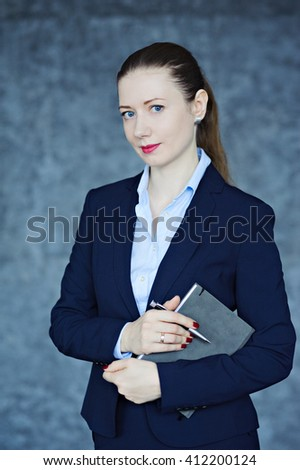 Beautiful young woman dressed in business style, with the diary in hand, textured background, look at the camera. - stock photo