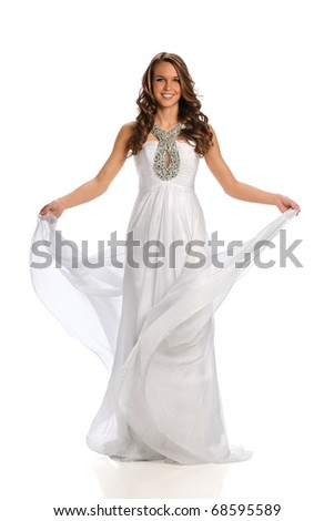 Beautiful young woman dressed in gown standing over white background
