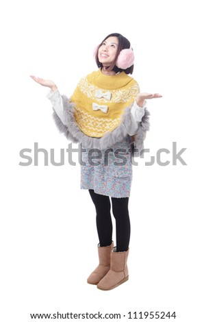 Beautiful young woman dressed in winter / autumn clothes smiling ,looking up, with hands open and waiting for snow or something else - stock photo