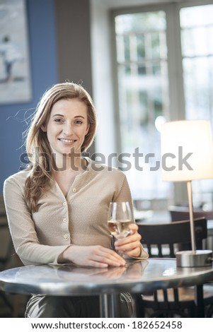 beautiful young woman drinking a wineglass alone in a bar